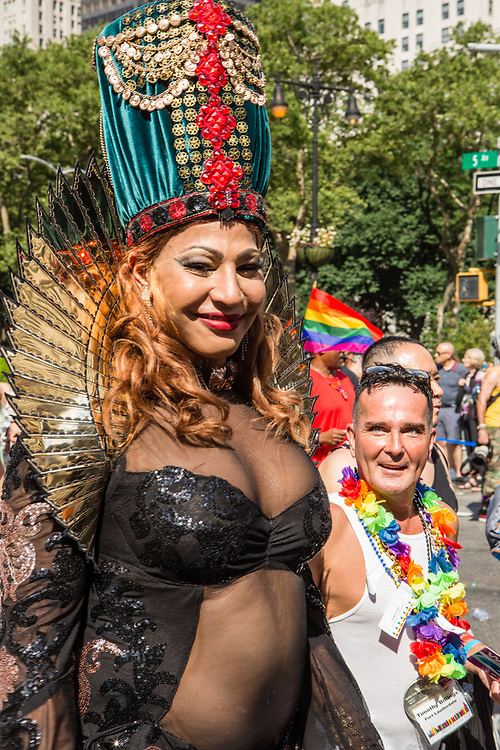 New York, NY - 25 June 2017. New York City Heritage of Pride March filled Fifth Avenue for hours with groups from the LGBT community and it's supporters. A marcher wears an elaborate and colorful headdress, which earns the admiring look of another marcher.
