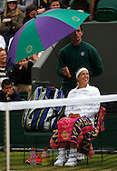 Wimbledon Championships 2012 AELTC,London,.ITF Grand Slam Tennis Tournament,.Sabine Lisicki (GER) sitzt unter dem Regenschirm und wartet,Einzelbild,Ganzkoerper,.Hochformat,schlechtes Wetter,kalt,Kaelte,