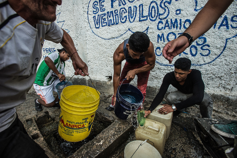 CARACAS, VENEZUELA - MAY 19, 2016:  People fill jugs and buckets with water from a well in the La Bombilla neighborhood in Petare slum. Several residents of La Bombilla said they have not had running water in their homes for nearly two years. Despite having the largest known oil reserves in the world, the Venezuelan government is having difficulties providing basic services like electricity and running water. They are currently rationing both. Most emblematic has been perhaps one of the most desperate measures ever by a government to save electricity: A shut down of nearly all government buildings to all but two (part-time) days each week. Government employees in Venezuela only go to work now on Mondays and Tuesdays.  All public schools now have a three-day weekend, taking off Fridays in order to save electricity.  PHOTO: Meridith Kohut