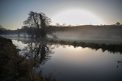 © Licensed to London News Pictures. 02/01/2017. Godalming, UK. Sunrise is reflected in the River Wey near Godalming. A cold spell is expected to remain for most of the next week. Photo credit: Peter Macdiarmid/LNP