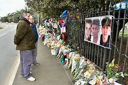 © Licensed to London News Pictures. 29/01/2018. London, UK.  People view photographs hanging on railings above floral tributes. George Wilkinson, 16, Harry Rice, 17, and Josh Mcgunnies, 16, were killed when a car mounted the pavement in Hayes, west London, on the night of 27 January. Jaynesh Chudasama, 28, of Hayes has been charged with three counts of causing death by dangerous driving and will appear in custody at Uxbridge Magistrates Court on Monday 29 January.  Photo credit: Stephen Chung/LNP