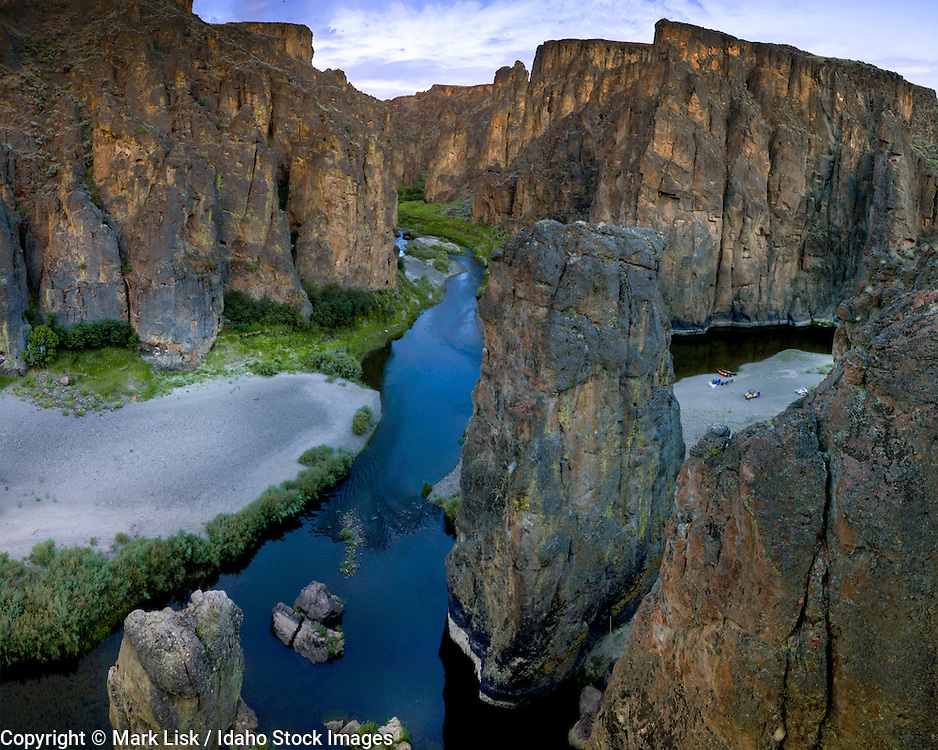 Canoeist take advantage of the low water of the Owyhee River and set up camp under giant rhyolite towers.