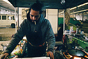 A man cooks at his food stall inside a warehouse at Napoli NYE Tek, a New Year's Eve party in Naples, Italy, December 2014