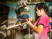 "29 DECEMBER 2018 - BANGKOK, THAILAND: A woman makes longevity noodles in her family shophouse. The family has been making traditional ""mee sua"" noodles, also called ""longevity noodles"" for three generations in their home in central Bangkok. They use a recipe brought to Thailand from China. Longevity noodles are thought to contribute to a long and healthy life and  are served on special occasions, especially Chinese New Year, which is February 4, 2019. These noodles were being made for Chinese New Year.     PHOTO BY JACK KURTZ"