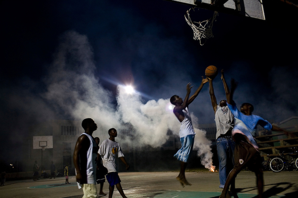 Kids play basketball at night in a poor part of Belize City, Belize