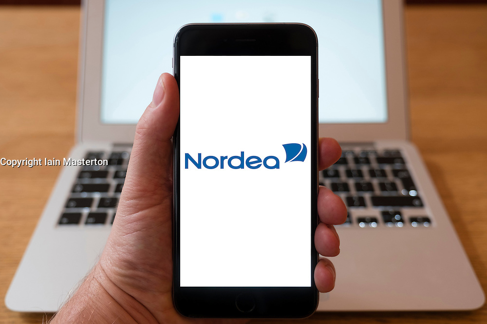 Using iPhone smart phone to display website logo of Nordea financial services company in Baltic and Nordic region