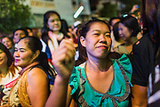 19 JANUARY 2014 - BANGKOK, THAILAND:  Members of the audience dance in spectators' area during a mor lam show in Khlong Tan Market in Bangkok. Mor Lam is a traditional Lao form of song in Laos and Isan (northeast Thailand). It is sometimes compared to American country music, song usually revolve around unrequited love, mor lam and the complexities of rural life. Mor Lam shows are an important part of festivals and fairs in rural Thailand. Mor lam has become very popular in Isan migrant communities in Bangkok. Once performed by bands and singers, live performances are now spectacles, involving several singers, a dance troupe and comedians. The dancers (or hang khreuang) in particular often wear fancy costumes, and singers go through several costume changes in the course of a performance. Prathom Bunteung Silp is one of the best known Mor Lam troupes in Thailand with more than 250 performers and a total crew of almost 300 people. The troupe has been performing for more 55 years. It forms every August and performs through June then breaks for the rainy season.              PHOTO BY JACK KURTZ
