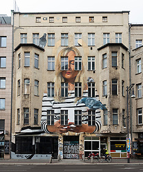 Large mural painted on facade of apartment building in Mitte, Berlin, Germany