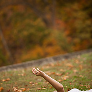 A woman lies in the grass near a trail in Rock Creek Park in Washington DC under Autumn leaves.