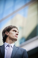 Low angle view of young businessman looking away with building in the background