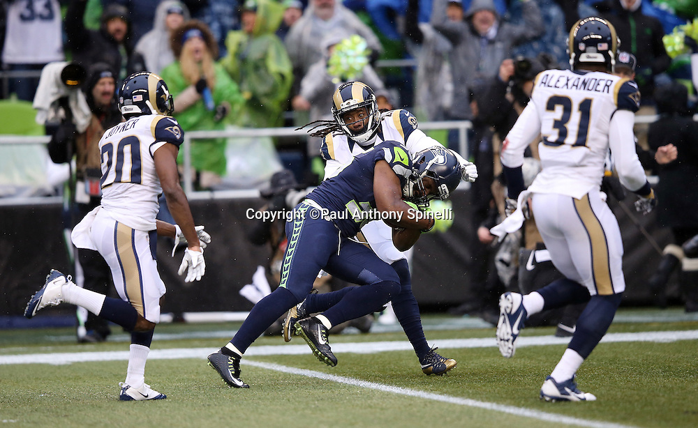 Seattle Seahawks running back Bryce Brown (36) is chased by St. Louis Rams cornerback Lamarcus Joyner (20), St. Louis Rams free safety Rodney McLeod (23), and St. Louis Rams strong safety Maurice Alexander (31) after catching a 31 yard pass reception negated by a second quarter penalty on the Seahawks during the 2015 NFL week 16 regular season football game against the St. Louis Rams on Sunday, Dec. 27, 2015 in Seattle. The Rams won the game 23-17. (©Paul Anthony Spinelli)