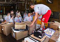 Tyler Mitza gets help from the entire Laconia Football team helped as they load furniture and supplies into storage during construction phase of the Laconia Fire Department on Friday morning.  (Karen Bobotas/for the Laconia Daily Sun)