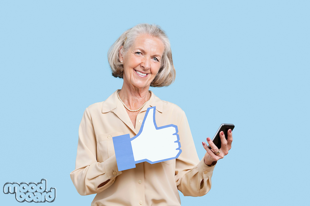 Portrait of senior woman with cell phone holding fake like button against blue background