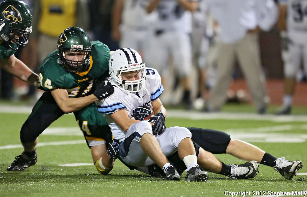 Jefferson's Nick O'Connell (5) is brought down behind the line of scrimmage for a loss by Kennedy's Thomas Kaiser (84) and David Hynek (44) during second quarter of the game between Cedar Rapids Jefferson and Cedar Rapids Kennedy at Kingston Stadium in Cedar Rapids on Friday September 28, 2012. It was 24-0 Kennedy at halftime.