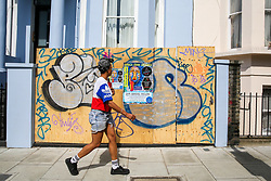 © Licensed to London News Pictures. 24/08/2019. London, UK. A woman walks past a residential property boarded up ahead of the 2019 Notting Hill Carnival which takes place this weekend and on bank holiday Monday. Up to 1 million people are expected to attend the biggest street party in Europe. Photo credit: Dinendra Haria/LNP
