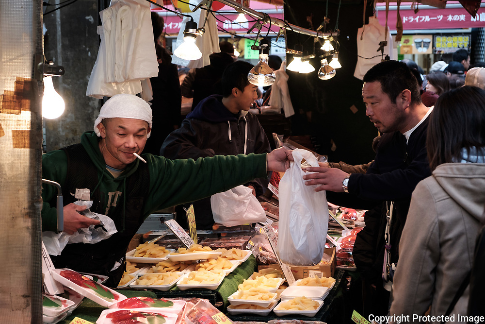 "A merchant serves a client at the Ameyoko market, Ueno in Tokyo Sunday, Dec. 31, 2017. Ameyoko market is crowded by shoppers who look for discounts on ingredients for ""osechi"" or Japanese traditional New Year dishes. 31/12/2017-Tokyo, JAPAN"