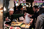 """A merchant serves a client at the Ameyoko market, Ueno in Tokyo Sunday, Dec. 31, 2017. Ameyoko market is crowded by shoppers who look for discounts on ingredients for """"osechi"""" or Japanese traditional New Year dishes. 31/12/2017-Tokyo, JAPAN"""
