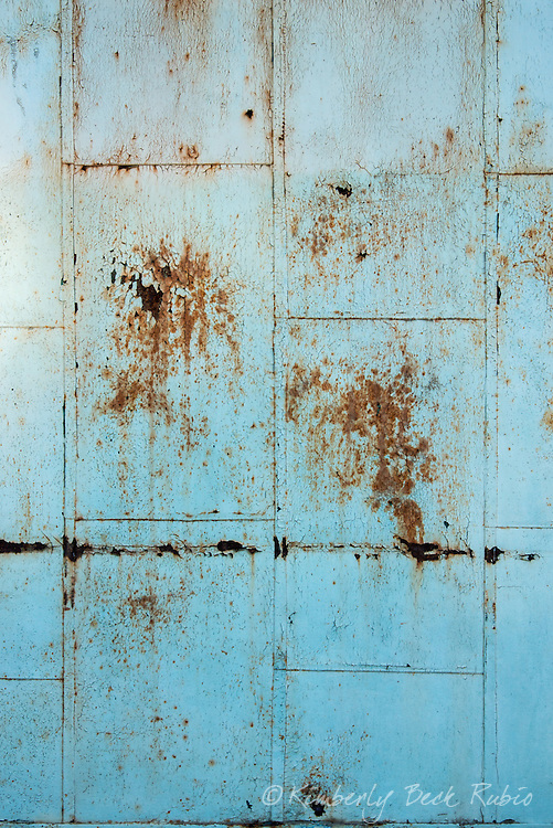 Detail of a rusted light-blue garage door at Winehaven, a dilapidated former California winery and Naval fuel depot at Point Molate in Richmond, California