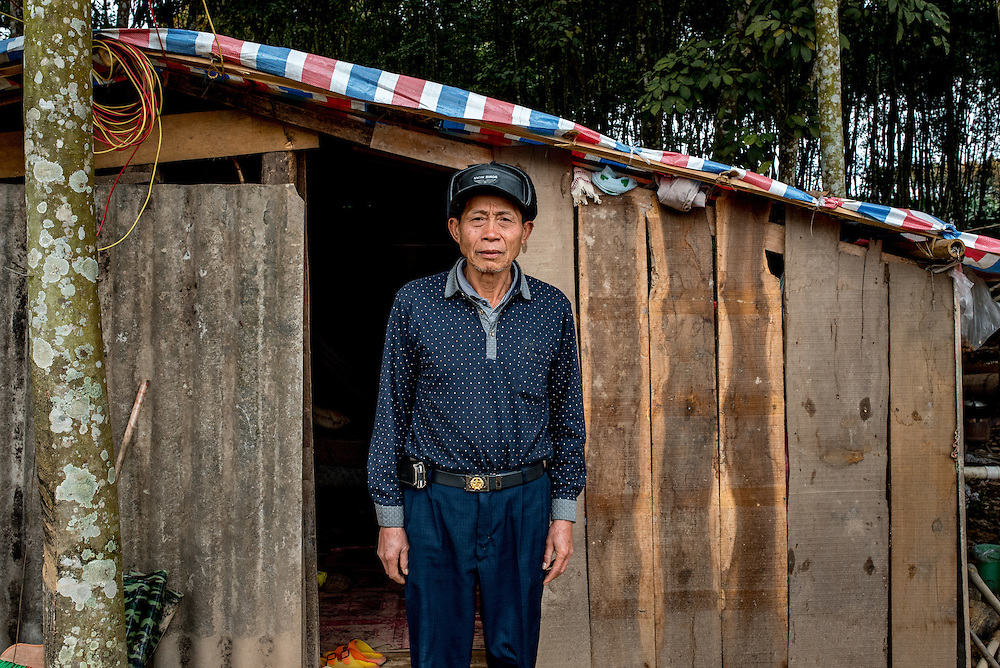 Yan Ying, 52, stands in front of his home in Manhenuan, Xishuangbanna, China. With the financial success of the nearby Dai minority cultural village at Olive Dam, residents of Manhenuan are trying to open their village up to tourism as well.