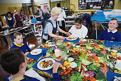 Children with physical and learning difficulties being served a meal at lunchtime,