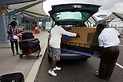 Unloading a bulky plasma flatscreen TV from vehicle at departures level of Heathrow's Terminal 5.