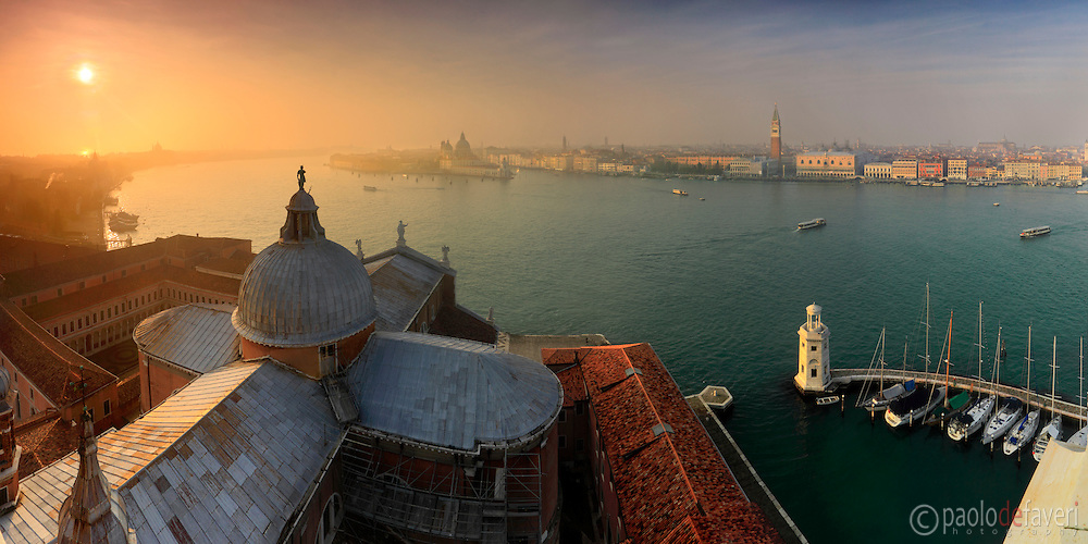 A panoramic view of the San Marco Basin as seen from the top of the bell tower of San Giorgio Maggiore, with the church of San Giorgio Maggiore in the foreground and, in the background, the Giudecca Canal on the left, Punta della Dogana and the entrance of the Grand Canal at the centre, San Marco square and bell tower, Doge's Palace and Riva degli Schiavoni on the right. A glorious sunset on a misty evening of mid January. Stitched from nine vertical frames.