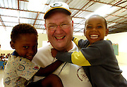 Archbishop Dolan hods two children during a visit to the Dominican Republic in 2006. (Sam Lucero photo)