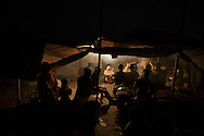 Displaced people from Angarpathra in Dhanbad, Jharkhand, India, light coal inside their tent on Dec 5, 2014. Forty five houses in the village collapsed as the earth caved in due to an underground coal fire on Nov 14. The government provided people who lost their homes about $200 but those who don't have money to re-build their houses live in tents.<br /> (Photo by Kuni Takahashi)