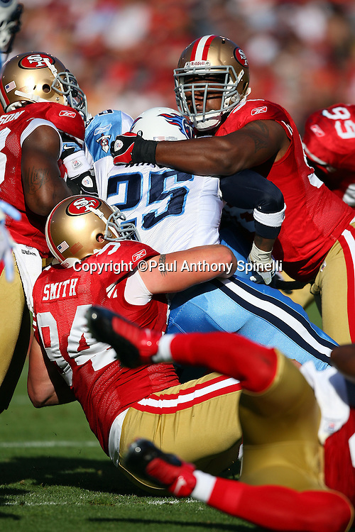 Tennessee Titans running back LenDale Whilte (25) gets gang tackled by San Francisco 49ers defensive tackles Justin Smith (94) and Kentwan Balmer (96) during the NFL football game against the San Francisco 49ers, November 8, 2009 in San Francisco, California. The Titans won the game 34-27. (©Paul Anthony Spinelli)