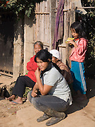 Burmese woman & child sitting outside house; Tachilek; Myanmar