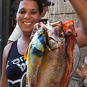 Fishing is not only a favorite pastime for Cubans but it is also an income source. A woman sells her daily catch in La Habana Vieja), old Havana. Photography by Jose More