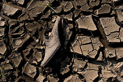 30 Sept, 2005.  New Orleans, Louisiana. Lower 9th ward. Hurricane Katrina aftermath. <br /> The remnants of the lives of ordinary folks, now covered in mud as the flood waters remain.  A woman's shoe lies stuck in the mud. <br /> Photo; ©Charlie Varley/varleypix.com