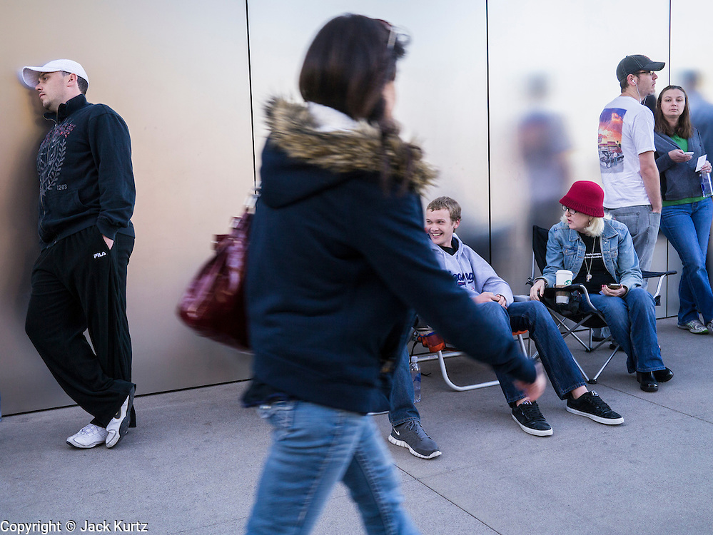 16 MARCH 2012 - SCOTTSDALE, AZ:  A pedestrian walks past people waiting in line to buy the New iPad in Scottsdale, AZ. Several hundred people were in line at the Apple Store in the Scottsdale Quarter in Scottsdale, AZ, Friday to buy the New iPad.   PHOTO BY JACK KURTZ