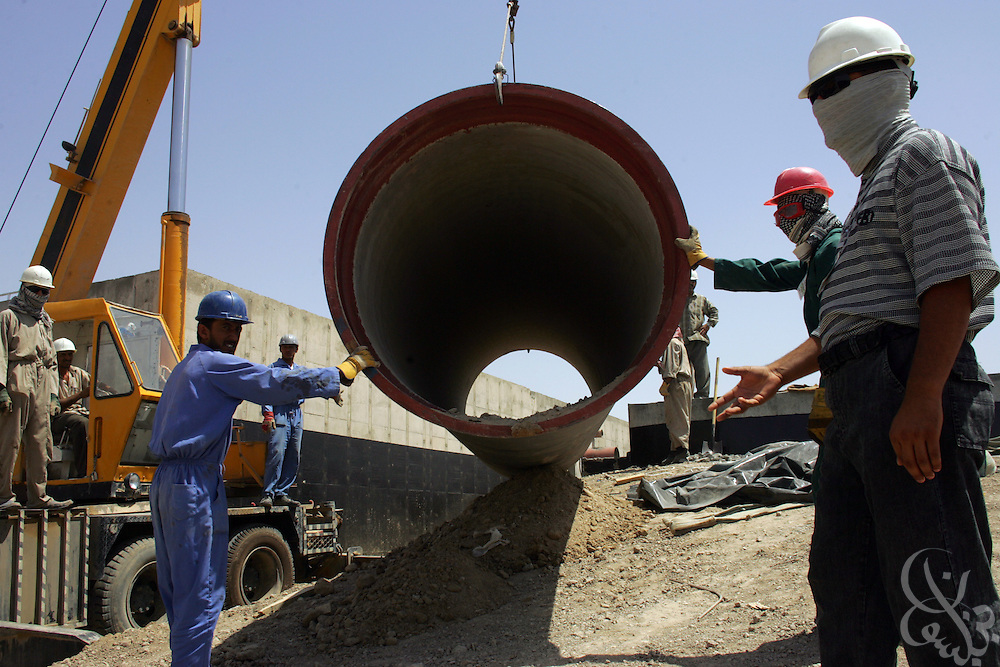 Iraqi contractors install piping for work on a water treatment plant project near the city of Kut, June 20, 2006.