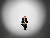 Businessman sitting under the spotlight