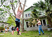 Esme Anderson, 10, swings from a rope while her siblings, Lucy Anderson, 15, Otto Anderson, 13, and Dean Anderson, 6, and her mom, author Bernadette Noll, right, hula hoop outside their south Austin home on Thurs., March 28, 2013.<br /> Ashley Landis for American-Statesman
