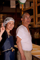 A father and daughter pose inside their handmade tofu shop on the streets of Kyoto, near Kiyomizudera Temple.