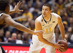 West Virginia Mountaineers guard Nathan Adrian (11) looks to pass against the Wofford terriers during the first half at the WVU Coliseum.