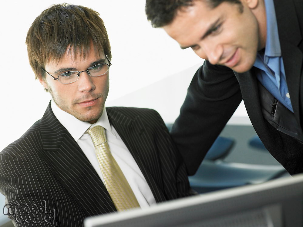 Two businessmen in office looking at computer screen