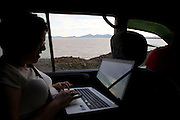 Catherine working in the back of the vehicle wight a lake view out to the window