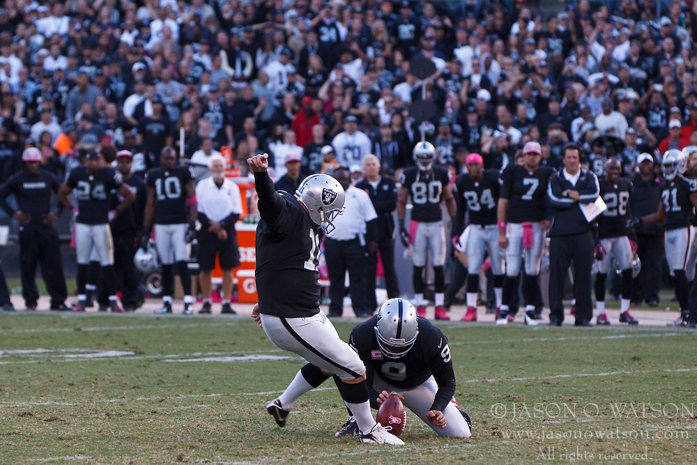OAKLAND, CA - OCTOBER 21: Kicker Sebastian Janikowski #11 of the Oakland Raiders kicks the game winning field goal off a hold from Shane Lechler #9 during overtime at O.co Coliseum on October 21, 2012 in Oakland, California. The Oakland Raiders defeated the Jacksonville Jaguars 26-23 in overtime. Photo by Jason O. Watson/Getty Images) *** Local Caption *** Sebastian Janikowski; Shane Lechler