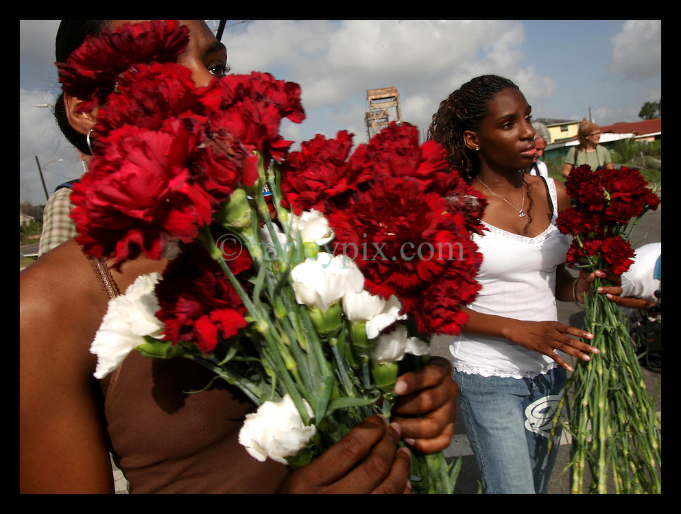 29 August 2006 - New Orleans - Louisiana. Lower 9th ward. Great Flood commemoration and memorial ceremony; to 'honor and remember our loved ones who have passed. <br />Twin sisters, 17 year old Whitney (rt) and Britney Bickham hand out red carnations to mourners as people prepare to pay tribute to and salute the victims of hurricane Katrina, which struck one year ago today.