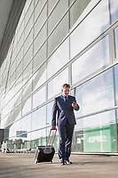Businessman using smartphone while walking with his suitcase in the airport
