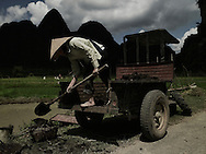 A vietnamese man with a conical hat unloads soil from his trunk. Cao Bang province, Vietnam, Asia.
