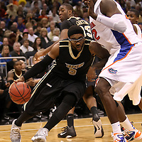 University of Central Florida guard Marcus Jordan (5) dribbles the ball past Vernon Macklin (32)  while taking on the Florida Gators at the Amway Center on December 1, 2010 in Orlando, Florida. Central Florida won the game 57-54 for their first ever victory against a nationally ranked team. (AP Photo/Alex Menendez)