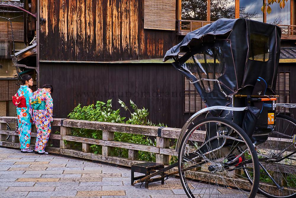 Japon, île de Honshu, région de Kansaï, Kyoto, Gion, ancien quartier des Geishas, jeunes femmes touristes en kimono se promenant en pousse-pouss // Japan, Honshu island, Kansai region, Kyoto, Gion, Geisha former area, young women in kimono travelling with local taxi