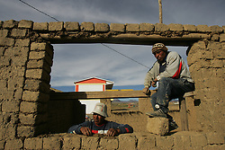 Workers build a home in Mariscal Sucre, a neighborhood in El Alto.   Many of the adobe homes in Mariscal Sucre have no running water and families are forced to collect rain water, use dirty wells or go to a nearby home with water.   The private water company, Aguas de Illimani, had their contract annulled by the Bolivian government after members of the politically powerful El Alto community took to the streets to protest poor service and high installation fees.