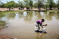 Nuanadro Murina (30) Kvinde ved sø med 4 børn 3,6,9,13 - hun vasker tøj i regnvands sø og har en lille bar med hjemmebryg, som hun lever af.