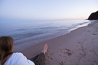 A woman relaxes on the red sand beach of Basinhead, PEI, to watch the sunset over the ocean.