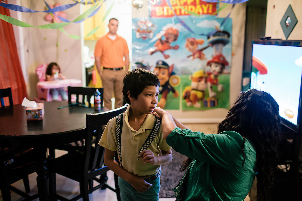 Larissa Camilleri puts suspenders on her son Eric, 8, as her husband, Matthew, looks on, early in the morning before school on March 17, 2015. Matthew, is in the Army, and when they moved to DC from Germany, Camilleri was pregnant with their third child, Scarlett. Instead of looking for housing in the competitive DC market, they moved into housing on the Joint Base Anacostia-Bolling in a few days.